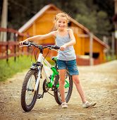 cute little girl with her bicycle in rural areas