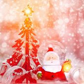 Beautiful Christmas still life, cute little Santa Claus toy and red small Christmas tree on pink blurry background, luxury festive home decoration