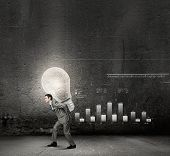Young businessman carrying light bulb on back