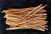 top view of breadsticks grissini torinesi on blackboard background