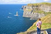 image of cliffs moher  - Young woman at The Cliff of Moher Co - JPG