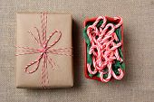 High angle shot of a bowl of mini candy canes next to a plain paper wrapped Christmas present on a burlap surface. The gift is tied with red and white twine. Horizontal Format.
