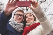 Amorous dates in winterwear taking selfie outdoors