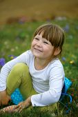 Little cheerful girl on a green meadow