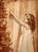 Little girl decorate on Christmas tree.