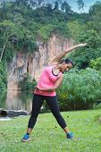 Sporty woman stretching right side of body after exercising in outdoor park