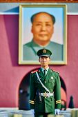 Beijing , China - September 24, 2014: Chinese soldier in front of the soldier in front of mao zedong poster portrait Tiananmen Square forbidden city Beijing China