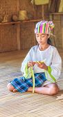 young beautiful child girl in traditional clothes in bamboo house making toys from palm leaves, Philippines, Malay, Panay