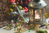 Christmas still life: lantern with burning candle and New Year tree decorations. Aperture 16