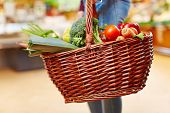Customer carrying full shopping basket with fresh vegetables in a supermarket
