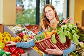 Attractive elderly woman buying fresh vegetables in organic food store