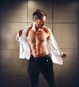 picture of undressing  - A businessman undresses of his elegant clothes - JPG