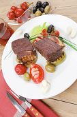 roast meat : beef (pork) steak garnished with baked apples , juice, green and black olives , tomatoes , on wooden table