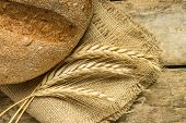 image of husbandry  - Fresh bread with wheat ears on wooden table - JPG