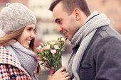 A picture of a romantic couple on a date holding flowers