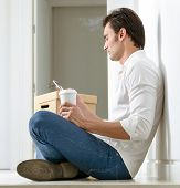 Man, with pile of boxes,  sitting on the floor with a coffee, checking his smart phone