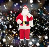 christmas, holidays and people concept - man in costume of santa claus with bag over snowy night city background
