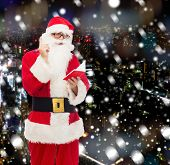 christmas, holidays and people concept - man in costume of santa claus with notepad and pen over snowy night city background