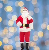 christmas, holidays and people concept - man in costume of santa claus with bag over blue lights background