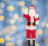christmas, holidays, gesture and people concept - man in costume of santa claus with bag pointing finger up over blue lights background