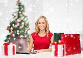 technology, holidays, e-commerce and people concept - woman with shopping bags and laptop computer over living room background