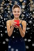holidays, christmas, presents, luxury and people concept - smiling woman in dress holding red gift box night lights and snow background