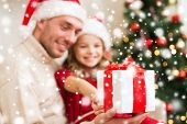 christmas, holidays, family and people concept - smiling father and daughter in santa hats holding gift box at home