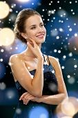 people, christmas, holidays and glamour concept - smiling woman in evening dress over black background over night lights and snow background