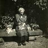 GERMANY, CIRCA THIRTIES:  Vintage photo of elderly woman in apron sitting on bench with Pekingese dogs