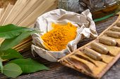 Tumeric powder spice on wooden board with tabletes as healthy supplement of diet