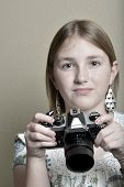 Detail portrait of young girl teenager photographer holding vintage old camera shooting photographs