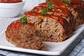 stock photo of meatloaf  - sliced meatloaf with ketchup and parsley closeup on a white plate horizontal - JPG