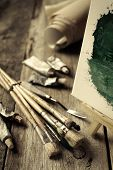 Artistic Paintbrushes, Tubes Of Oil Paint, Palette Knife And Easel With Oil Painting On Old Wooden D