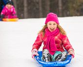 picture of toboggan  - Happy girl expressing joy while sledding in the snow in winter.