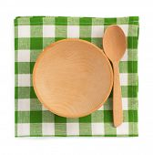 wooden plate at checked napkin on white background