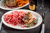 Pasta with steak on wooden table