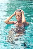 Young Asian woman meditating in a swimming pool standing chest high in the water with her eyes closed and arms raised to her head with a serene expression