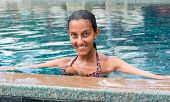 Happy smiling Asian woman on summer vacation standing chest high in the refreshing blue water of a swimming pool smiling at the camera
