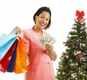 Beautiful African-american woman holding shopping bags and money.  Isolated on white, in front of a Christmas tree.