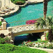 Beautiful Resort Swimming Pool With Sun Chairs, Bridge And Flowe