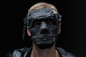 picture of madman  - Image of madman in handmade mask on black background - JPG