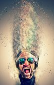 image of disc jockey  - Crazy screaming disc jockey with headphones and a lot of explosion particles flying get over the air - JPG