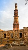 picture of qutub minar  - Grave markers with a stone wall and the qutub minar at the back - JPG