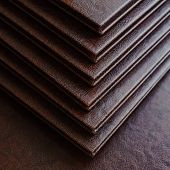 picture of hardcover book  - top view of a stack of books in a brown leather hardcover closeup