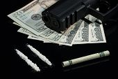 stock photo of gun shot  - Close up shot of cocaine US dollars an a gun on black background - JPG