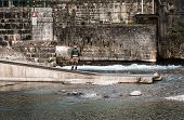image of trout fishing  - Fisherman on the river Serio while fishing. Typical trout fishing. ** Note: Visible grain at 100%, best at smaller sizes - JPG