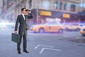 picture of binoculars  - Businessman looking through binoculars against blurred new york street - JPG