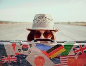 stock photo of old suitcase  - Hipster girl in a hat looks out from vintage suitcase - JPG