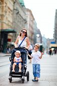 Mother And Two Kids Walking In City Center
