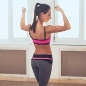 foto of bicep  - Active athletic sporty woman in sport outfit standing showing biceps muscles of the back and buttocks rear view healthy lifestyle - JPG
